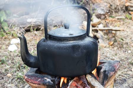 79746153-the-old-kettle-the-water-is-boiling-boil-the-water-in-the-kettle-on-handmade-stove-made-of-cement